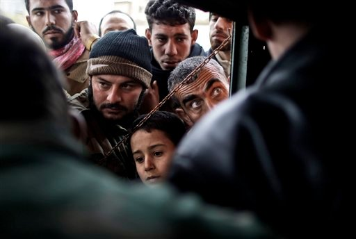 © In this Thursday, Dec. 13, 2012, photo, people gather by the window of a makeshift post where Free Syrian Army fighters sell bread, in Maaret Misreen, near Idlib, Syria.