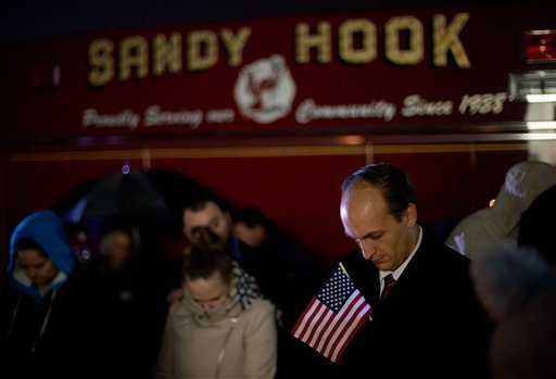 © Mourners listen to a memorial service over a loudspeaker outside Newtown High School for the victims of the Sandy Hook Elementary School shooting, Sunday, Dec. 16, 2012, in Newtown, Conn.