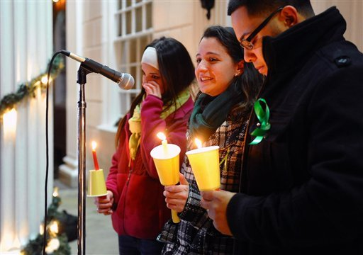 Jillian Soto, center, thanks the hundreds of people who came out to attend a candlelight vigil in memory of victims from the mass shooting in Newtown, Conn., which was held behind Stratford High School on the Town Hall Green in Stratford, Conn. (AP Photo)