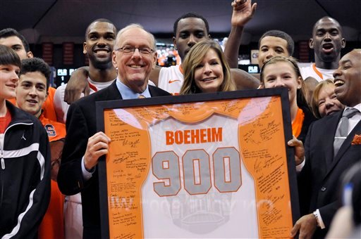 © Syracuse coach Jim Boeheim, joined by his wife, Julie, is presented with a jersey for his 900th career win, after Syracuse defeated Detroit 72-68 in an NCAA college basketball game in Syracuse, N.Y., Monday, Dec. 17, 2012.