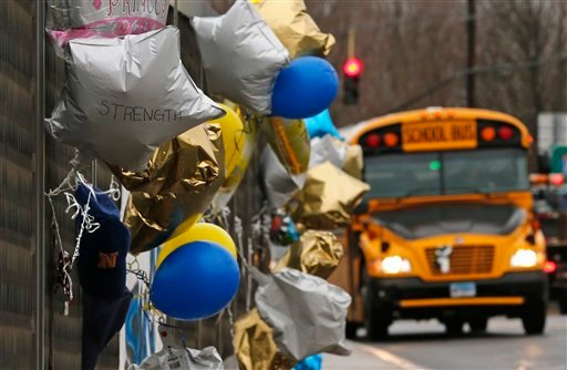 A school bus rolls towards a memorial for victims of the school shooting in Newtown, Conn., Tuesday, Dec. 18, 2012. Classes resume Tuesday for Newtown schools except those at Sandy Hook.
