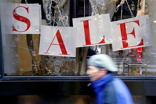 In this Tuesday, Dec. 18, 2012, photo, a person passes a retail store with sale sign displayed in the window in Philadelphia.  (AP Photo/Matt Rourke)
