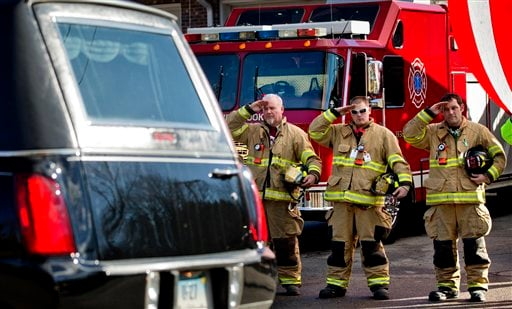 Firefighters salute as a hearse passes for the funeral procession to the burial of 7-year-old Sandy Hook Elementary School shooting victim Daniel Gerard Barden, Wednesday, Dec. 19, 2012, in Newtown, Conn.(AP Photo/David Goldman)