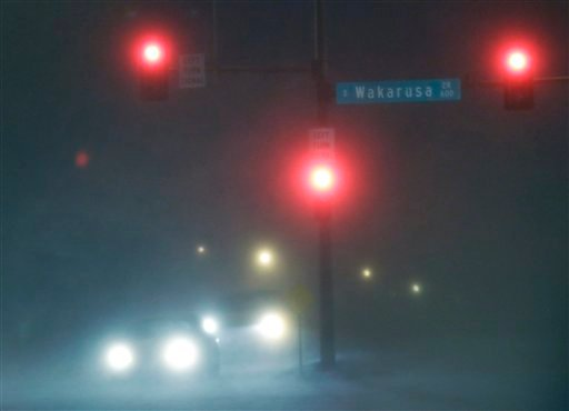 Blowing snow reduces vision as motorists wait for a light change in Lawrence, Kan., Thursday, Dec. 20, 2012. (AP Photo/Orlin Wagner)