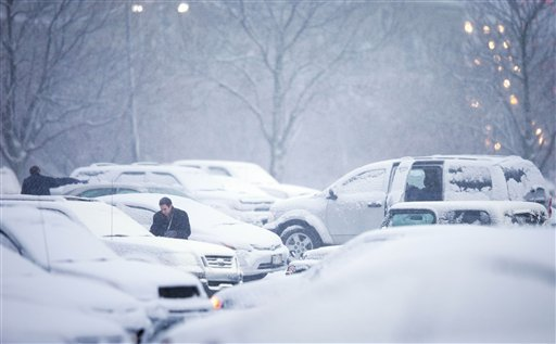 Mutual of Omaha employees clean their vehicles of snow before leaving on their drive home during the evening commute Wednesday Dec. 20, 2012 in Omaha Neb. (AP Photo/The World-Herald, Matt Miller)