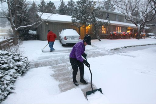 A woman and her husband shovel their walk as a blizzard dropped snow over Boulder, Colo., Wednesday Dec. 19, 2012. (AP Photo/Brennan Linsley)