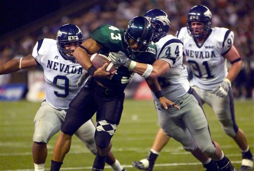 In this Oct. 9, 2004, file photo, Hawaii's Bryan Maneafaiga (43) scores a touchdown against Nevada in Honolulu. (AP Photo/ Honolulu Star-Advertiser, George F. Lee)