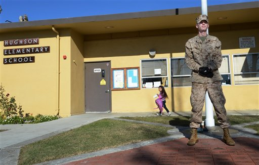 U.S Marine Corps Reserve Sgt. Craig Pusley stands guard as kindergarten student Liset Corona, 5, walks to her class at Hughson Elementary School on Wednesday morning Dec. 19, 2012 in Hughson, Calif. (AP Photo/The Modesto Bee, Ed Crisostomo)
