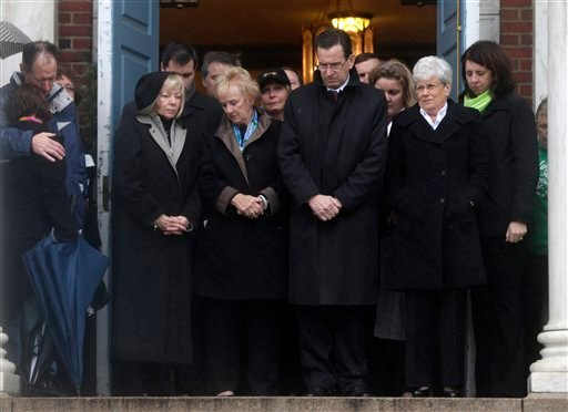 © Connecticut Gov. Dan Malloy, center, stands with other officials to observe a moment of silence while bells ring 26 times in Newtown, Conn., Friday, Dec. 21, 2012, in honor of the victims who were killed last Friday during the shooting at Sandy Hook.