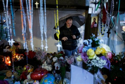 © Ben Toby of Sandy Hook visits a memorial to the Newtown shooting victims during a heavy rain in the Sandy Hook village of Newtown, Conn., Friday, Dec. 21, 2012.