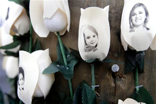 © Photos showing those killed in the shootings at Sandy Hook Elementary School are imprinted on fake roses at a memorial in the Sandy Hook village of Newtown, Conn., Saturday, Dec. 22, 2012. (AP Photo/Seth Wenig)