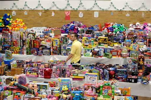© Volunteer Anthony Vessicchio of East Haven, Conn., helps to sort tables full of donated toys at the town hall in Newtown, Conn., Friday, Dec. 21, 2012. (AP Photo/Seth Wenig)