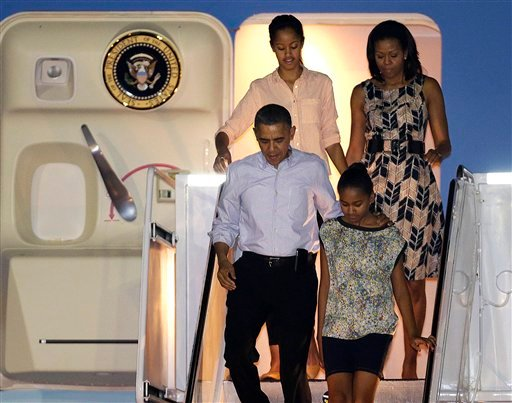 © President Barack Obama arrives with first lady Michelle Obama, top, and daughters Malia, top left, and Sasha, bottom right, at Honolulu Joint Base Pearl Harbor-Hickam in Honolulu, for the start of their holiday vacation, Saturday, Dec. 22, 2012.