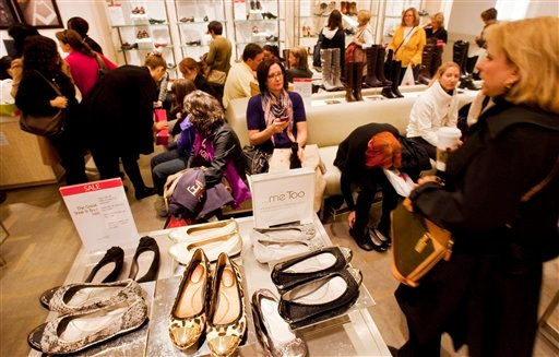 © In this photo of Friday, Oct. 12, 2012, customers shop at Macy's shoe department in New York. Shoes are coming out of the closet and landing under the Christmas tree.