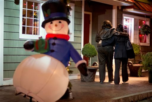 © In this Dec. 19, 2012 file photo, mourners walk past a Frosty the Snowman Christmas decoration after visiting a memorial for the Sandy Hook Elementary School shooting victims, in Newtown, Conn. In the wake of the shooting.
