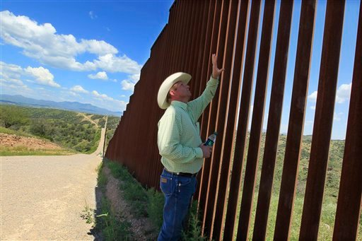 © In this Friday, Aug. 10, 2012 photo, rancher Dan Bell checks out part of the property he leases at the border fence between the United States and Mexico, in Nogales, Ariz.