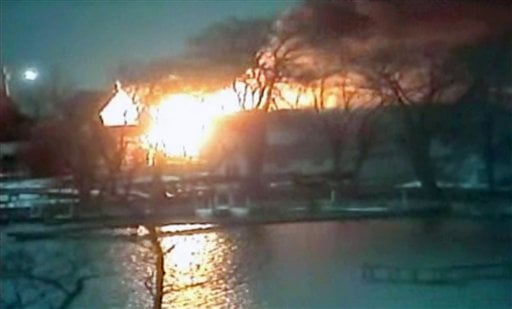 © This image taken from video provided by WHAM13-TV, shows a wide view of homes on fire in an area where a gunman ambushed four volunteer firefighters responding to an intense pre-dawn house fire early Monday, Dec. 24, 2012, in Webster, N.Y.