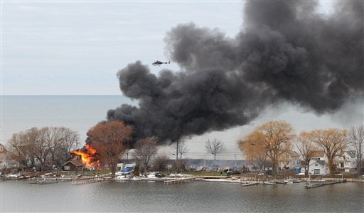 A house burns Monday, Dec. 24, 2012 in Webster, New York. An ex-con set a car and a house ablaze in his lakeside neighborhood to lure firefighters, then opened fire on them, killing two. (AP Photo)