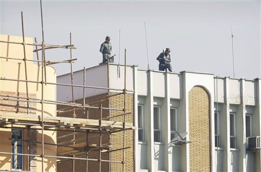 © Afghan policemen watching down from top of the Kabul police headquarters, following the killing of an American advisor in Kabul, Afghanistan, Monday, Dec. 24, 2012.