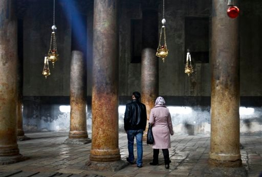 People walk inside the Church of Nativity, traditionally believed by Christians to be the birthplace of Jesus Christ, ahead of Christmas, in the West Bank town of Bethlehem, Sunday, Dec. 23, 2012. (AP Photo/Nasser Shiyoukhi)