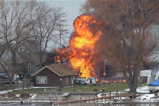 © A house burns Monday, Dec. 24, 2012 in Webster, New York. A former convict set a house and car ablaze in his lakeside New York state neighborhood to lure firefighters then opened fire on them, killing two and engaging police in a shootout.