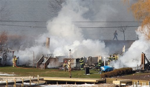 © Firefighters battle a blaze after they were let back in, Monday Dec. 24, 2012, in Webster, N.Y.