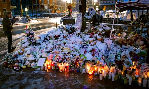 © A member of the Rutter family of Sandy Hook, Conn., walks past candles and other offerings that make up a memorial in Newtown, Conn., Tuesday, Dec. 25, 2012.