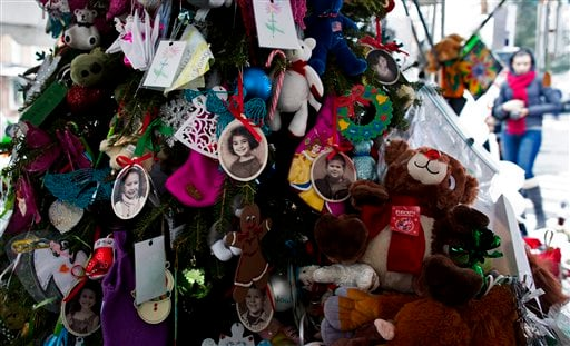  Portraits of slain students and teachers hang from a tree at a memorial in Newtown, Conn. Tuesday, Dec. 25, 2012.