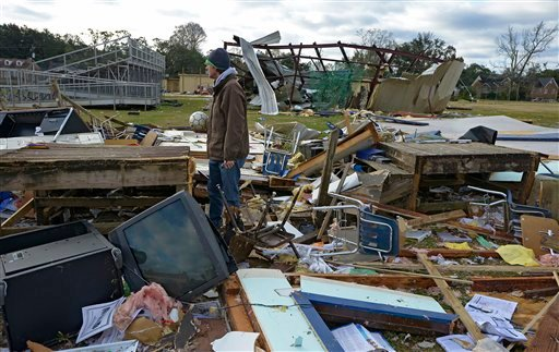 Murphy High School teacher Leland Howard tries to salvage items where his algebra classroom once stood in a temporary building at Murphy High School as residents clean up and assess the damage from a Christmas Day tornado Wednesday, Dec. 26, 2012. (AP)