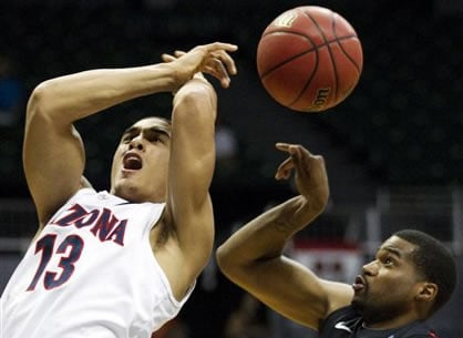 Arizona guard Nick Johnson (13) has the basketball stripped away from behind by San Diego State guard Chase Tapley (22) in the first half of an NCAA college basketball game at the Diamond Head Classic, Tuesday, Dec. 25, 2012, in Honolulu. (AP Photo)