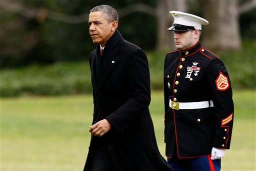 President Barack Obama walks past a Marine honor guard as he steps off the Marine One helicopter and walks on the South Lawn at the White House in Washington, Thursday, Dec. 27, 2012, as he returned early from his Hawaii vacation. (AP)