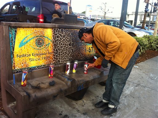 Phil Furtado places candles on a burned city bus bench in Los Angeles on Thursday Dec. 27,2012. (AP)