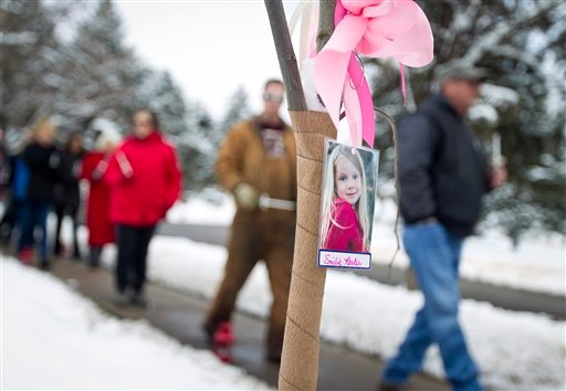 Visitors pass by a tree bearing the photo of Emilie Parker during the community dedication of a grove of trees at the Salt Lake City cemetery in remembrance of victims of the Newtown, Conn. shootings, Thursday, Dec. 27, 2012. (AP)