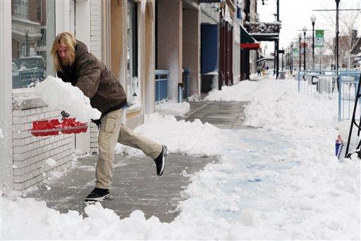 Scott Becker shovels the sidewalks of businesses along Main Street in downtown Evansville, Ind., on Thursday morning, Dec. 27, 2012. (AP Photo/The Evansville Courier & Press, Erin McCracken)