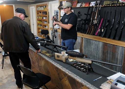 FILE - In this Thursday, Dec. 20, 2012 file photo, Clerk Lance McCoy, right, shows a variety of weapons including an AR-15 style semi-automatic at Kizer Guns and Ammo near Nacogdoches, Texas. (AP Photo/The Daily Sentinel, Andrew D. Brosig, File)