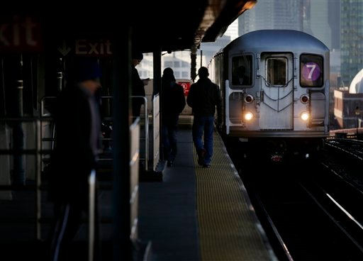 Commuters walk on the platform as a train enters the 40th St-Lowry St Station, where a man was killed after being pushed onto the subway tracks, in the Queens section of New York, Friday, Dec. 28, 2012. (AP Photo/Seth Wenig)