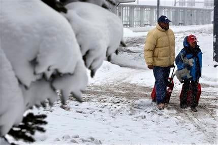 People walk in the snow at Buffalo Niagara International Airport in Buffalo, N.Y., Saturday, Dec. 29, 2012. (AP Photo/Mel Evans)