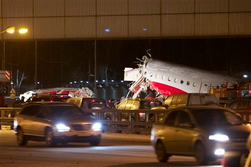 Cars travel past the wreckage of a plane that careered off the runway at Vnukovo Airport in Moscow, Saturday, Dec. 29, 2012. (AP Photo/Ivan Sekretarev)