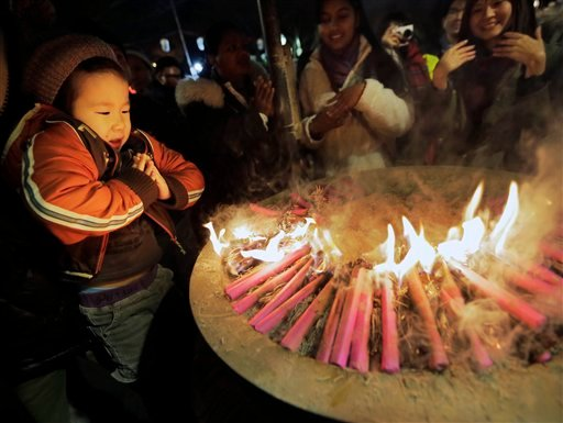 A boy prays around a fire believed to invoke divine help during their first visit of the year to the Zojoji Buddhist temple in Tokyo, Monday, Dec. 31, 2012.(AP Photo/Itsuo Inouye)