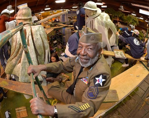 "Korean War veteran James McEachin, 82, poses in front of the Rose Parade float ""Freedom Is Not Free"" by the Korean War Commemoration Committee, Saturday, Dec. 29, 2012, in Pasadena, Calif. (AP Photo/Mark J. Terrill)"