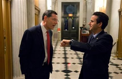 Sen. John Barrasso, left, R-Wyo., talks with Sen. Brian Schatz, D-Hawaii, who holds up his watch, near the Senate chambers after a vote on the fiscal cliff, on Capitol Hill Tuesday, Jan. 1, 2013. (AP Photo/Alex Brandon)