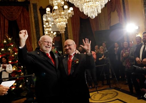 James Scales, left, and William Tasker react after participating in a wedding ceremony at City Hall in Baltimore, Tuesday, Jan. 1, 2013. (AP Photo/Patrick Semansky)