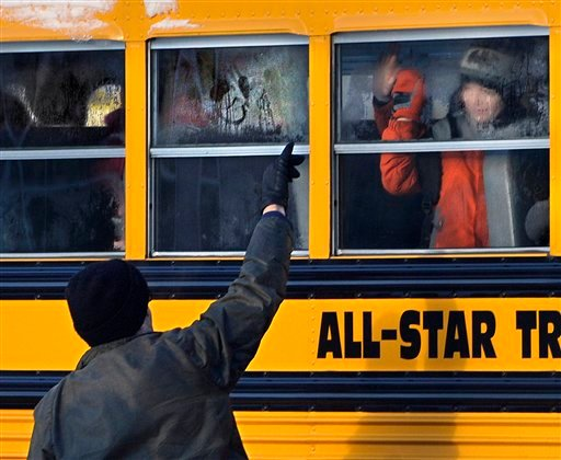 A man waves to a child on a bus on the first day of classes after the holiday break, in Newtown, Conn.,Wednesday, Jan. 2, 2013. (AP Photo/Jessica Hill)