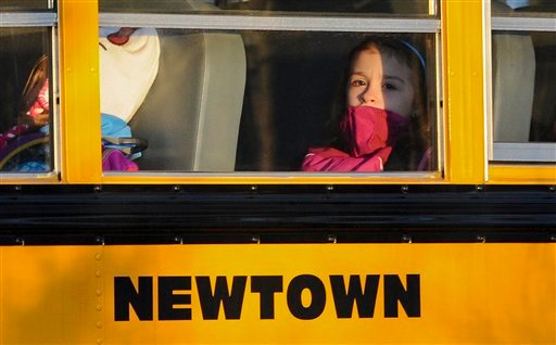  A girl sits on a Newtown bus leaving the new Sandy Hook Elementary School after the first day of classes in Monroe, Conn., Thursday, Jan. 3, 2013.