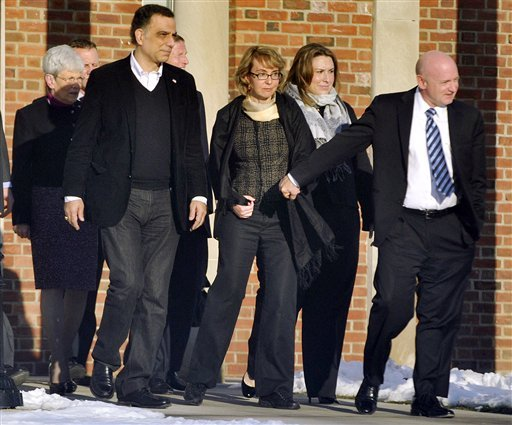 Former U.S. Rep. Gabrielle Giffords, center, holds hands with her husband, Mark Kelly, while exiting Town Hall at Fairfield Hills Campus in Newtown, Conn. after meeting with Newtown First Selectman Pat Llodra and other officials on Friday, Jan. 4, 2013.
