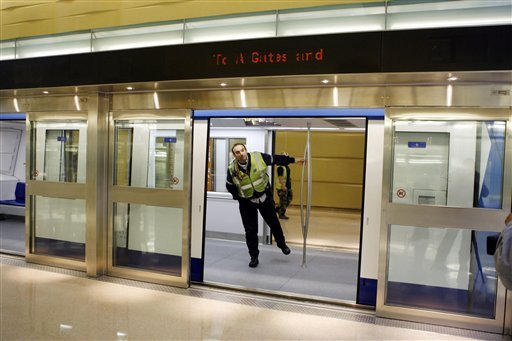 ©  In this Jan. 25, 2010 file photo, an airport worker looks out of the car and through the open doorway of the glass security barrier at Washington Dulles International Airport in Washington.