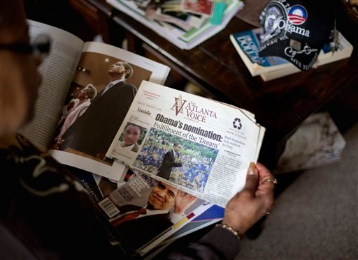 © This Jan. 2, 2013, photo, shows Victoria Wimberley, who will be attending President Barack Obama's inauguration for the second time, looking over some of the memorabilia in her home in Decatur, Ga.