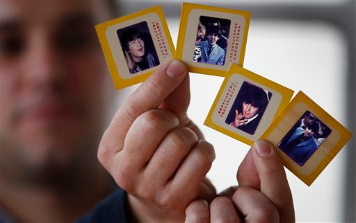 © In this photo taken Dec. 29, 2012, auctioneer Paul Fairweather holds four colour transparencies of The Beatles taken during their first tour of the USA in 1964.