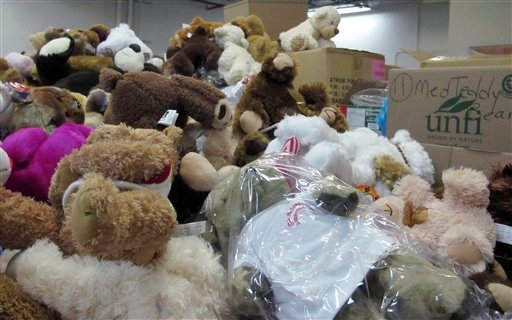 © In this Monday, Dec. 31, 2012 photo, piles of donated stuffed animals await sorting in a warehouse in Newtown, Conn.