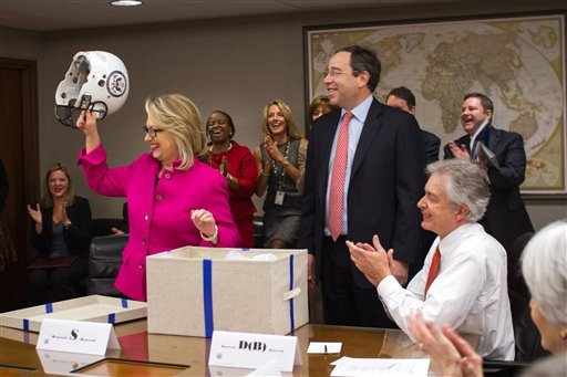 © This photo provided by the United States Department of State shows Secretary of State Hillary Rodham Clinton holding up a football helmet presented to her at the State Department in Washington, Monday, Jan. 7, 2013. (AP)